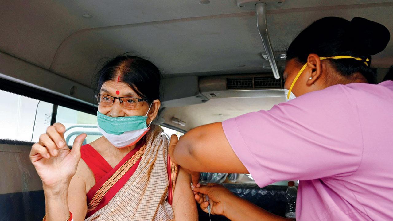 કોલકત્તામાં એક વૃદ્ધ મહિલાને વૅક્સિન આપતી આરોગ્ય કર્મચારી (તસવીરઃ એએફપી)