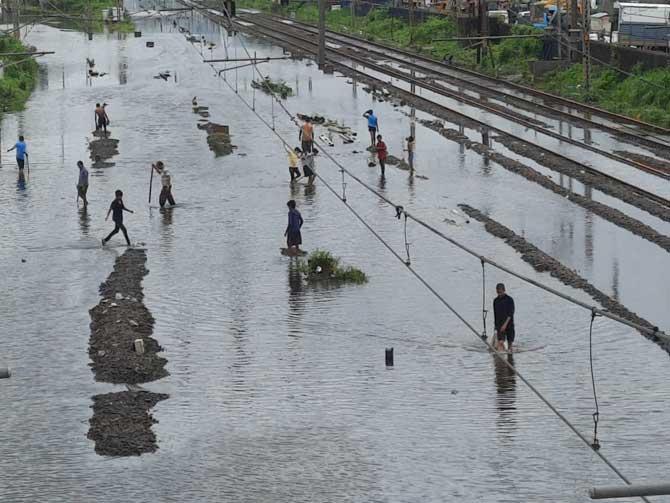 દક્ષિણ મુંબઈના નળ બજારની શેરીઓ ભરાયેલા પાણીથી બચવા લોકો ડિવાઇડર ઉપર ચાલે છે તસવીર: બિપીન કોકાટે