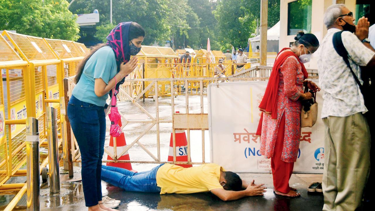 બાપ્પા, હવે નિયંત્રણો હળવાં કરાવજે. આવી જ પ્રાર્થના મુંબઈગરા સિદ્ધિવિનાયક મંદિરની બહાર કરી રહ્યાં હોવાનું લાગે છે (તસવીરઃ પ્રદીપ ધિવાર)
