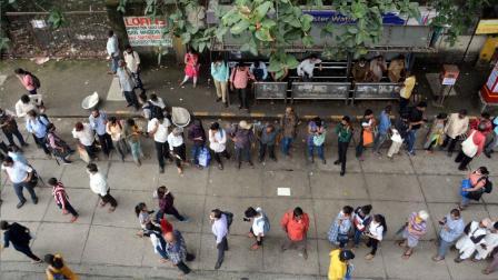 મુબંઈમાં બસ સ્ટોપ પર લોકોની લાઈન ( તસવીરઃ સાતેજ શિંદે)