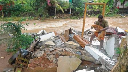 કેરલાના થોડુપુઝામાં ભારે વરસાદને કારણે કાટમાળમાં ફેરવાયેલા ઘરમાંથી પોતાના ડૉગીને સલામત રીતે લઈ જતો યુવક
